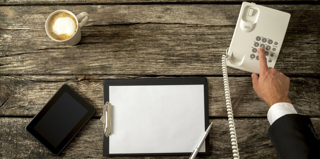 Job seeker with a piece of paper writing down the most important components of feedback for telecommuters.